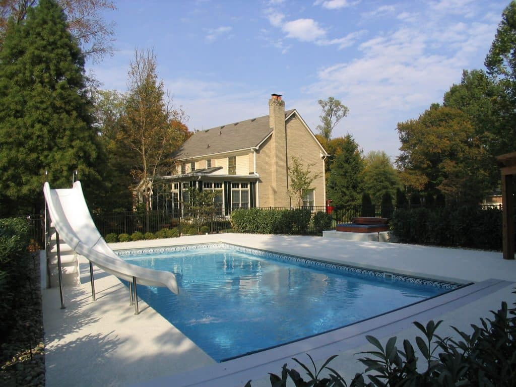 an in-ground pool with a slide and automatic cover