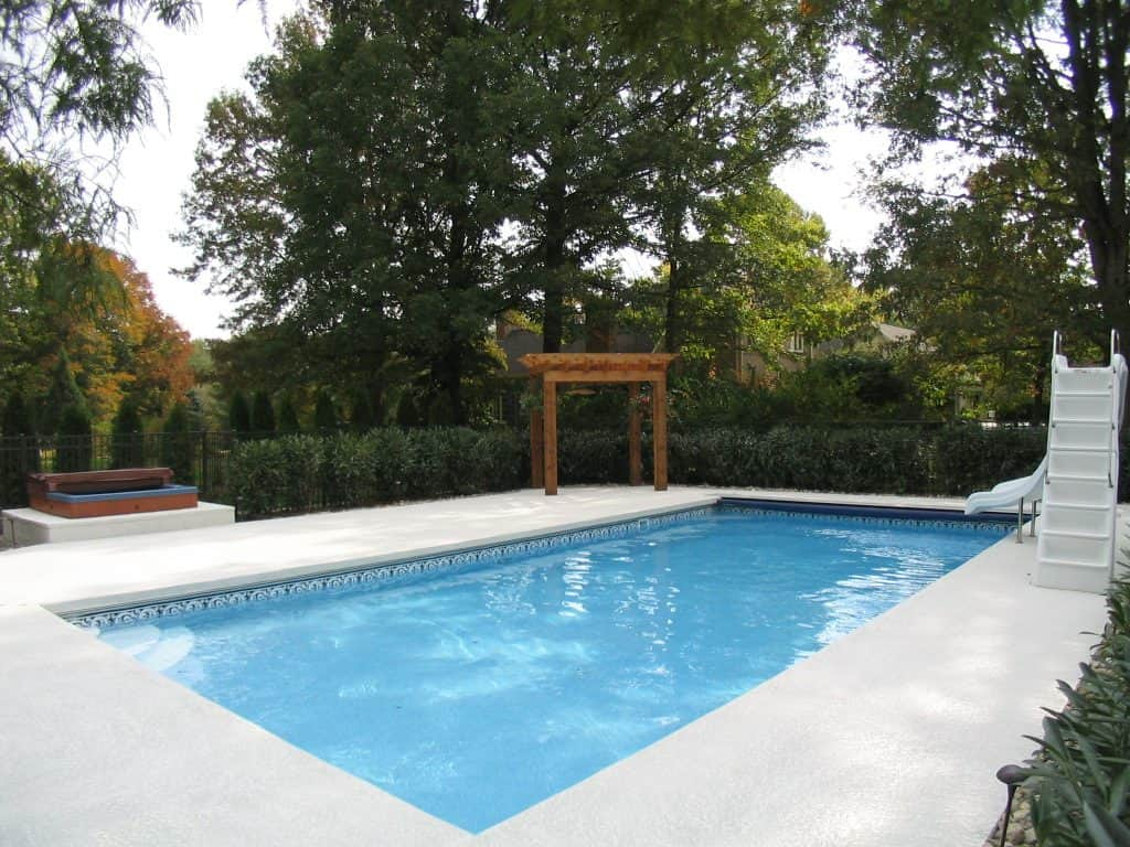 an in ground pool with a pergola