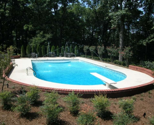 an in-ground pool with multiple fountains