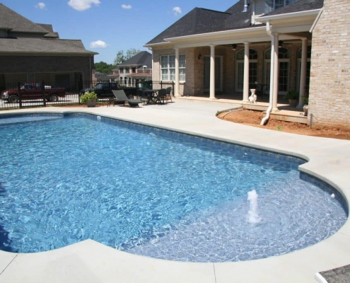 a pool with a fountain and sitting area
