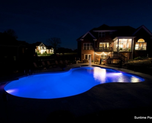 A in-ground pool lit up with underwater lights at night
