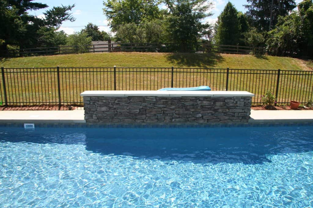 a wall next to an in-ground pool