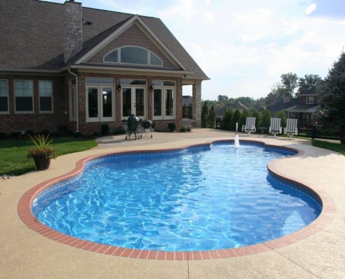 an inground free form pool with a big green egg
