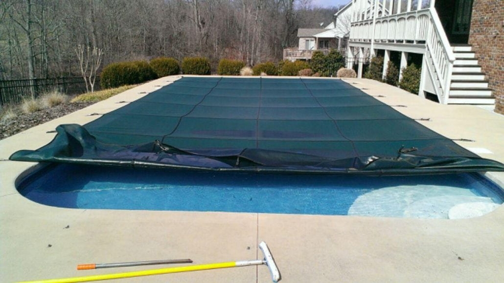 pool with a safety pool cover being removed